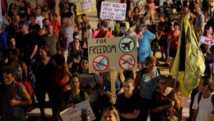 Israelis lift placards at a rally denouncing the governments renewed restrictions to combat COVID-19, in the central coastal city of Tel Aviv, on July 31, 2021. - Israel was quick to roll out its vaccination campaign and had dropped many restrictions on public gatherings in June, as new COVID-19 cases shrank from 10,000 a day to less than 100. But infections have soared in recent weeks, and masks are once again mandatory in enclosed public places, leading to the announcement on July 29 of the start of a vaccine booster campaign for over 60s, as concern mounts over the fast-spreading Delta variant of the coronavirus. (Photo by Ahmad GHARABLI / AFP)