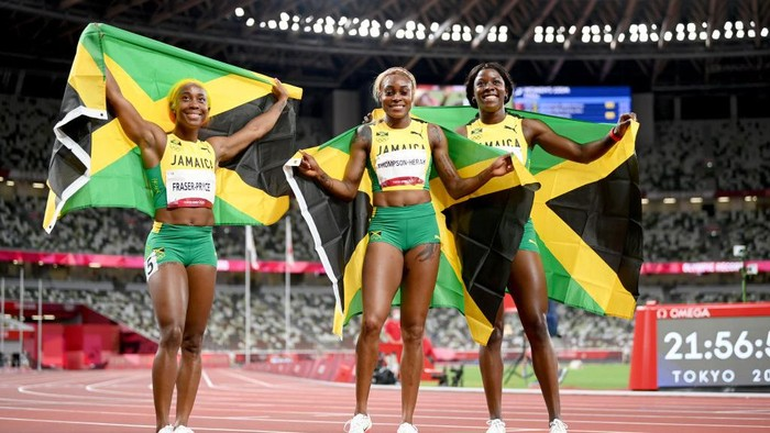 TOKYO, JAPAN - JULY 31: (L-R) Shelly-Ann Fraser-Pryce, Elaine Thompson-Herah and Shericka Jackson of Team Jamaica celebrate after completing a podium sweep in the Womens 100m Final on day eight of the Tokyo 2020 Olympic Games at Olympic Stadium on July 31, 2021 in Tokyo, Japan. (Photo by Matthias Hangst/Getty Images)