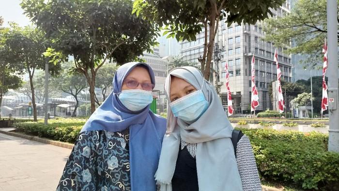 Hana (kanan) bersama ibunya, Ninik (kiri) berharap PPKM level 4 di Jakarta tak diperpanjang, Jl Sudirman, Jakarta, Minggu (1/8/2021).