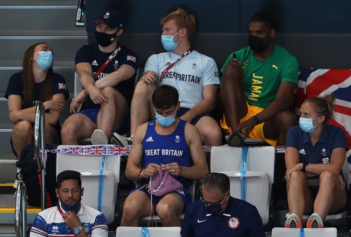 TOKYO, JAPAN - AUGUST 01: Tom Daley of Great Britain knits as he watches the Womens 3m Springboard Final on day nine of the Tokyo 2020 Olympic Games at Tokyo Aquatics Centre on August 01, 2021 in Tokyo, Japan. (Photo by Clive Rose/Getty Images)