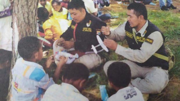 Polisi anggota Binmas Noken berinteraksi dengan anak-anak di Papua