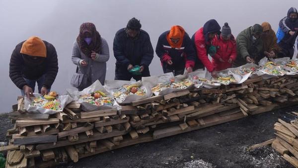 Orang-orang menyiapkan persembahan untuk menghormati Pachamama, atau Ibu Pertiwi, di La Cumbre, sebuah gunung yang dianggap suci di pinggiran La Paz, Bolivia, Minggu, 1 Agustus 2021.