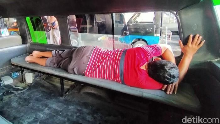 Kebijakan PPKM di tengah pandemi COVID-19 berdampak pada sektor transportasi. Salah satu di Surabaya, para sopir angkot pun mengakui pendapatan menurun drastis.