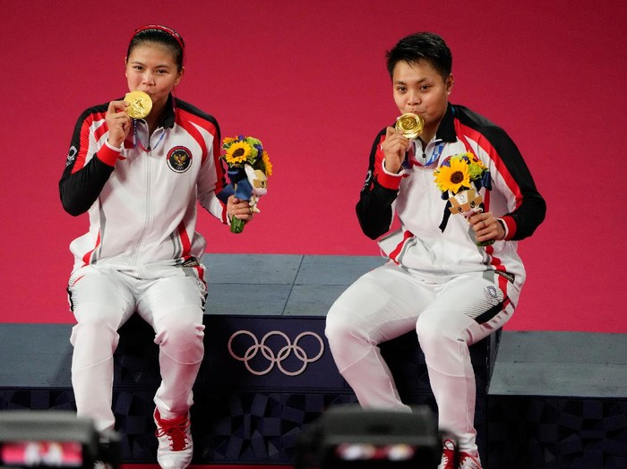 Gold medalists Greysia Polii, left, and Apriyani Rahayu from Indonesia celebrate during the medals ceremony of the womens doubles gold medal match at the 2020 Summer Olympics, Monday, Aug. 2, 2021, in Tokyo, Japan. (AP Photo/Markus Schreiber)