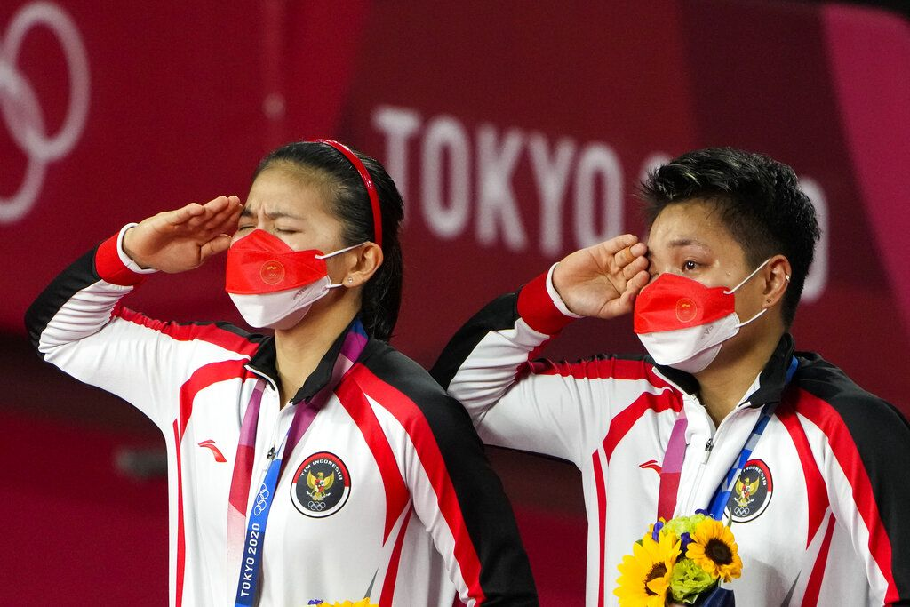 Gold medalists Greysia Polii, left, and Apriyani Rahayu from Indonesia listen to the national anthem during the medals ceremony of the women's doubles gold medal match at the 2020 Summer Olympics, Monday, Aug. 2, 2021, in Tokyo, Japan. (AP Photo/Markus Schreiber)