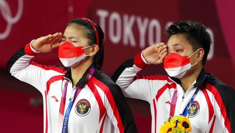 Gold medalists Greysia Polii, left, and Apriyani Rahayu from Indonesia listen to the national anthem during the medals ceremony of the womens doubles gold medal match at the 2020 Summer Olympics, Monday, Aug. 2, 2021, in Tokyo, Japan. (AP Photo/Markus Schreiber)