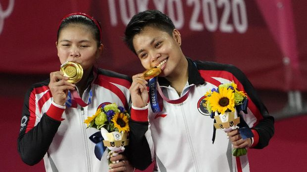Gold medalists Greysia Polii, left, and Apriyani Rahayu from Indonesia celebrate during the medals ceremony of the women's doubles gold medal match at the 2020 Summer Olympics, Monday, Aug. 2, 2021, in Tokyo, Japan. (AP Photo/Markus Schreiber)