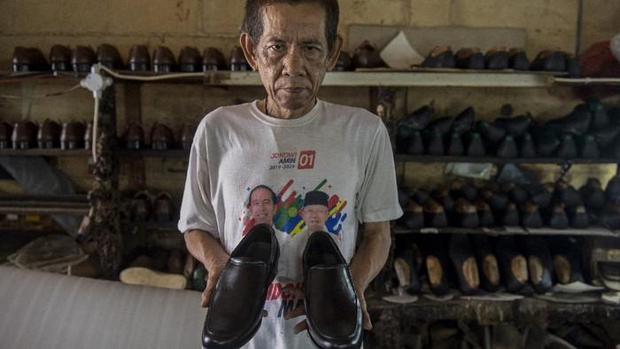 Pekerja menyelesaikan pesanan sepatu di bengkel kerja pembuatan sepatu milik Ardian di Perkampungan Industri Kecil (PIK) Penggilingan, Cakung, Jakarta Timur, Senin (2/8/2021). Adanya Pemberlakuan Pembatasan Kegiatan Masyarakat (PPKM) menyebabkan usahanya menurun hingga 70 persen dikarenakan toko-toko dan pusat perbelanjaan yang mengambil sepatu darinya tidak boleh berjualan. ANTARA FOTO/M Risyal Hidayat/foc.