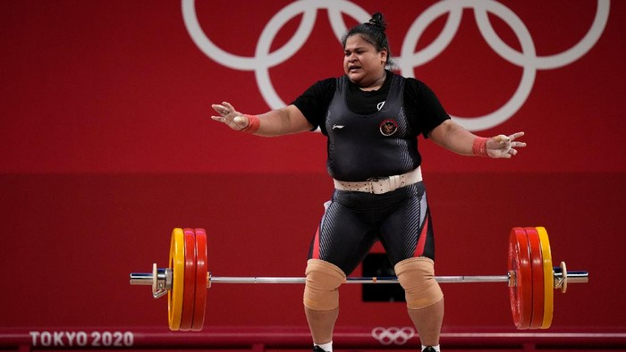 Nurul Akmal of Indonesia drops the barbell during a lift, in the womens +87kg weightlifting event at the 2020 Summer Olympics, Monday, Aug. 2, 2021, in Tokyo, Japan. (AP Photo/Luca Bruno)