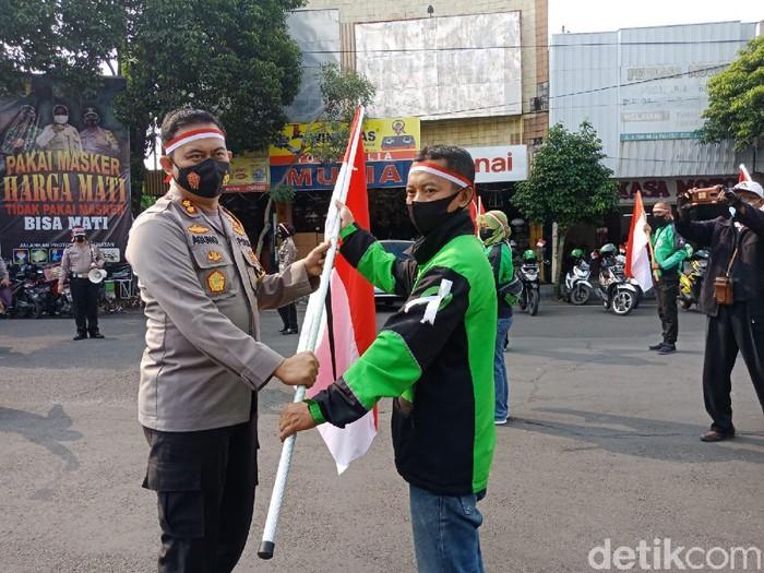Para PKL dan ojol di Jombang diajak mengibarkan Bendera Merah Putih. Aksi ini untuk menggelorakan semangat perjuangan melawan pandemi COVID-19.