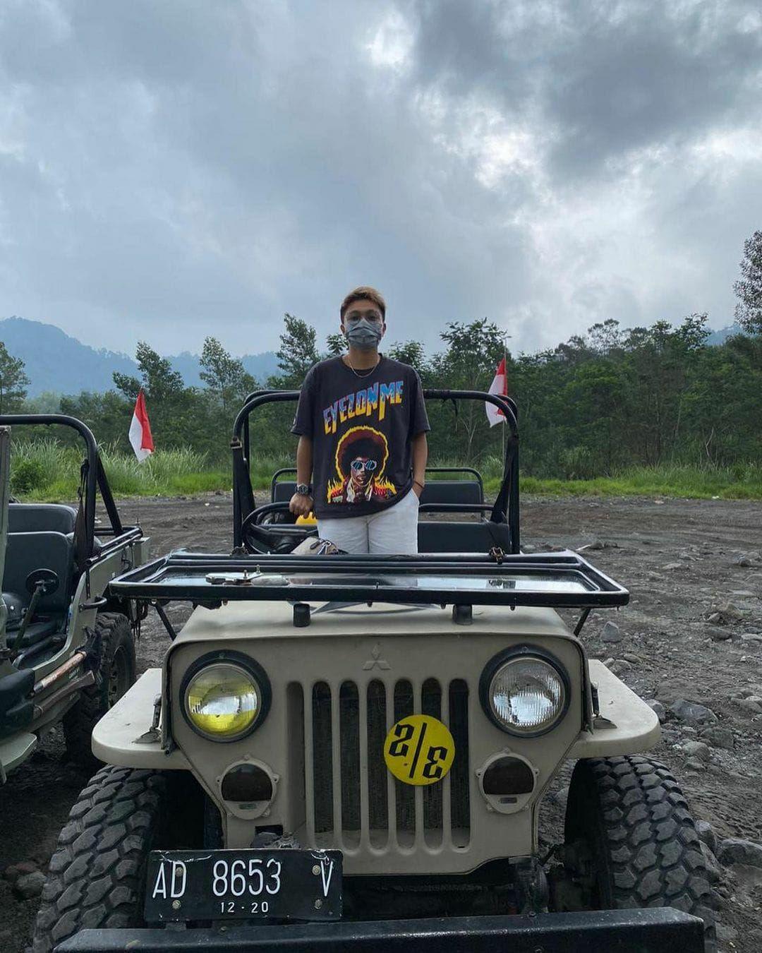 Pose Apriyani Rahayu di atas mobil Jeep Willys. Bersama Greysia Polii, Apriyani berhasil meraih medali emas Olimpiade Tokyo 2020 di kategori ganda putri.