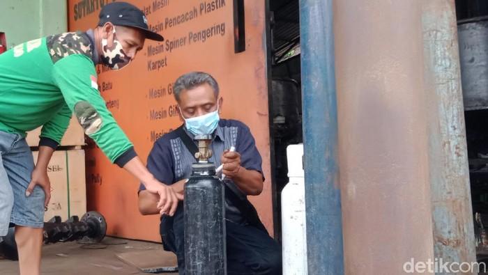 Sutarto saat mengisi tabung oksigen salah seorang warga yang datang ke bengkelnya di Klaten, Senin (2/8/2021)