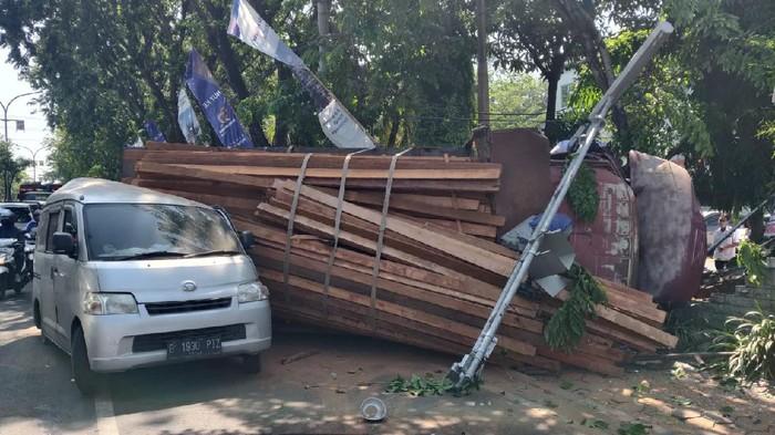 Truk bermuatan kayu terguling di Gresik diduga karena rem blong. Akibatnya, muatan tersebut menimpa sebuah mobil dan dua pengendara motor.
