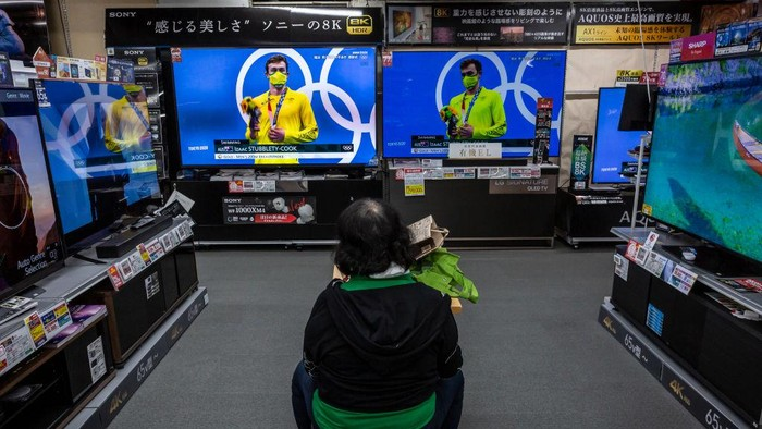 TOKYO, JAPAN - JULY 29: A woman watches Olympics games on televisions at an electronics retail store on July 29, 2021 in Tokyo, Japan. Fans have been barred from most Olympic events due to the Covid-19 pandemic, which also caused the Games yearlong postponement. (Photo by Yuichi Yamazaki/Getty Images)