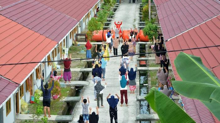 Seorang nakes memandu pasien COVID-19 untuk senam sore di tempat isolasi Perumahan Nelayan, Padang, Sumatera Barat, Selasa (3/8/2021). Fasilitas isolasi pasien COVID-19 terpusat dikelola Pemkot Padang tersebut memiliki jumlah pasien masuk yang terus meningkat sejak bulan Mei 2021, dengan data terakhir pada Juli sebanyak 537 pasien. ANTARA FOTO/Iggoy el Fitra/hp.