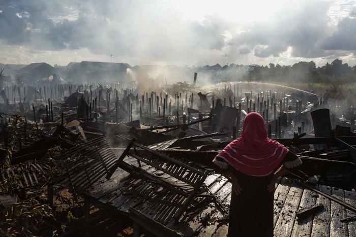 Seorang warga melihat rumahnya yang hangus terbakar di permukiman padat penduduk di Kelurahan Tumbang Rungan, Palangkaraya, Kalimantan Tengah, Selasa (3/8/2021). Kebakaran yang terjadi pada pukul 14.00 WIB tersebut menghanguskan sebanyak 29 rumah dan satu sarang burung walet, sementara penyebab terjadinya kebakaran masih dalam penyelidikan. ANTARA FOTO/Makna Zaezar/hp.
