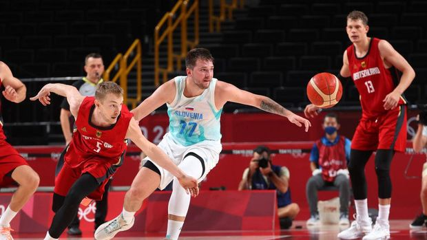 SAITAMA, JAPAN - AUGUST 03: Niels Giffey #5 of Team Germany and Luka Doncic #77 of Team Slovenia reach for a loose ball during the second half of a Men's Basketball Quarterfinal game on day eleven of the Tokyo 2020 Olympic Games at Saitama Super Arena on August 03, 2021 in Saitama, Japan. (Photo by Gregory Shamus/Getty Images)