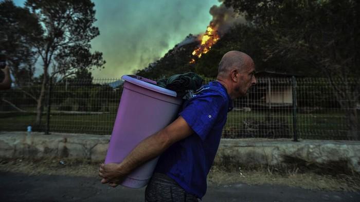 Kebakaran hutan melanda sejumlah kawasan Turki. Api yang masih terus berkobar membuat sejumlah warga memilih untuk mengungsi ke tempat yang lebih aman.
