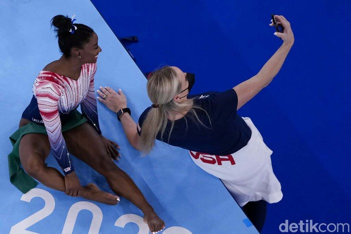 Coach Cecile Landi takes a selfie with Simone Biles, of the United States, during the warm up prior to the artistic gymnastics balance beam final at the 2020 Summer Olympics, Tuesday, Aug. 3, 2021, in Tokyo, Japan. (AP Photo/Morry Gash)