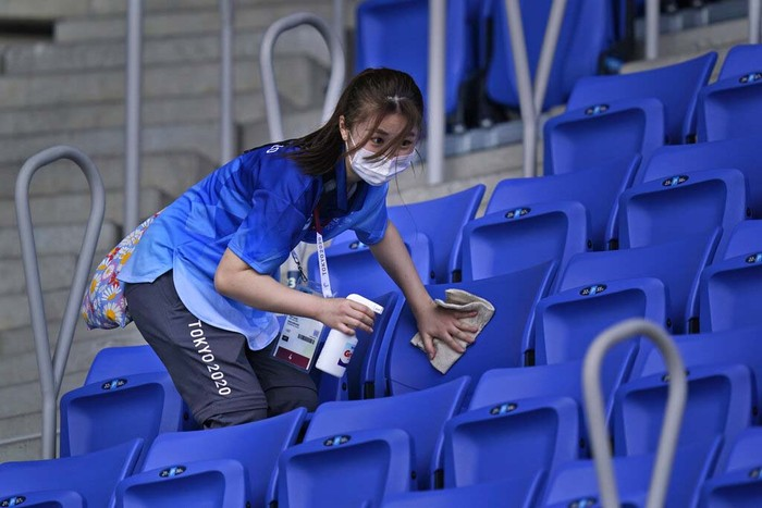 A volunteer cleans seats meant for spectators at the Ariake Tennis Center ahead of the 2020 Summer Olympics, Friday, July 23, 2021, in Tokyo, Japan. (AP Photo/Seth Wenig)