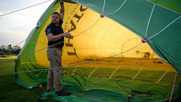 Seorang warga bersiap menerbangkan balon udara.