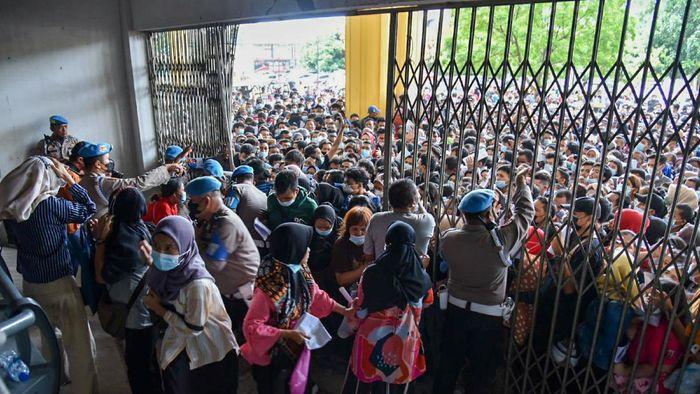 Warga antre untuk melakukan vaksinasi di aula Gedung Serbaguna Pemprov Sumatera Utara, Kota Medan, Selasa (3/8/2021). Ratusan warga berdesakan untuk mengikuti vaksinasi yang diselenggarakan oleh Polda Sumatera Utara. ANTARA FOTO/Fransisco Carolio/Lmo/hp.