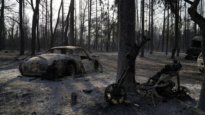 Burned vehicles after a wildfire in Varibobi area, northern Athens, Greece, Wednesday, Aug. 4, 2021. Firefighting planes were resuming operation at first light Wednesday to tackle a major forest fire on the northern outskirts of Athens which raced into residential areas the previous day, forcing thousands to flee their homes amid Greece's worst heatwave in decades. (AP Photo/Thanassis Stavrakis)