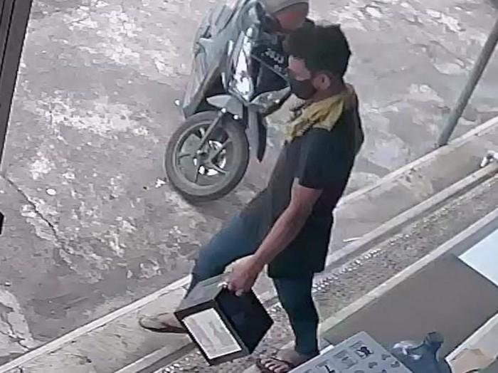 Seorang pria menggondol kotak amal milik yayasan yatim piatu, dari sebuah minimarket di Kecamatan Glagah, Banyuwangi. Aksi pelaku terekam CCTV toko tersebut.