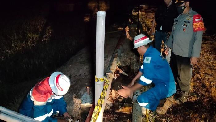 Petugas perbaiki pipa minyak Pertamina yang bocor.