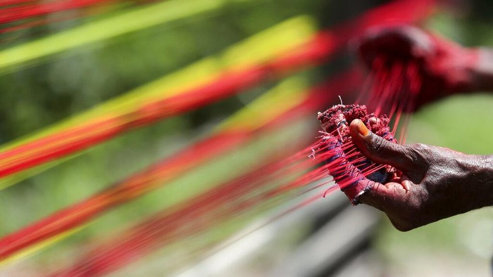 An Indian thread maker prepares colored threads for flying kites in Jammu, India, Tuesday, Aug. 3, 2021. The demand for these threads goes up in August when people in northern India fly kites and peaks during Independence Day, which falls on August 15. (AP Photo/Channi Anand)