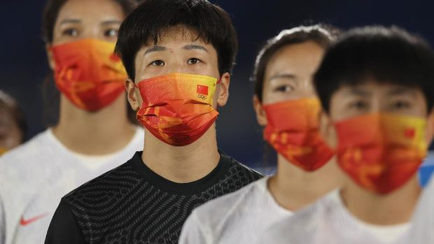 YOKOHAMA, JAPAN - JULY 27: Shimeng Peng #12 of Team China wears a face mask with teammates as they stand for the national anthem prior to the Women's Group F match between Netherlands and China on day four of the Tokyo 2020 Olympic Games at International Stadium Yokohama on July 27, 2021 in Yokohama, Kanagawa, Japan. (Photo by Francois Nel/Getty Images)
