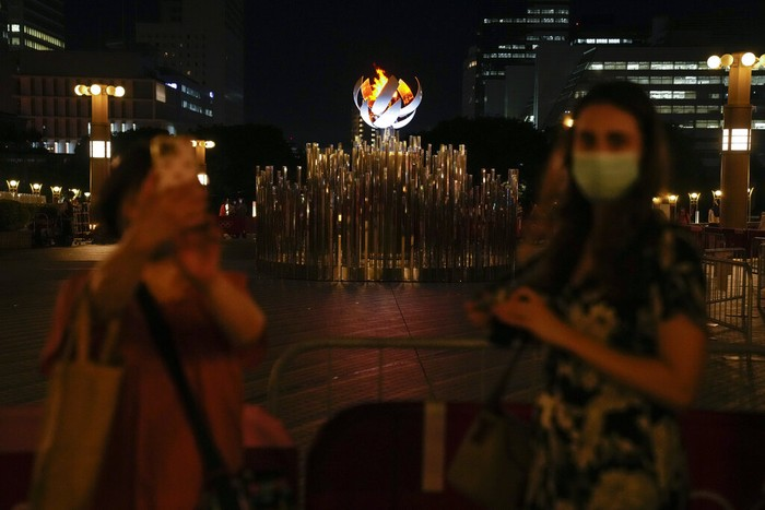 Two women take photos with the Tokyo 2020 Olympic Cauldron, Wednesday, Aug. 4, 2021, in Tokyo, Japan. (AP Photo/Ashley Landis)
