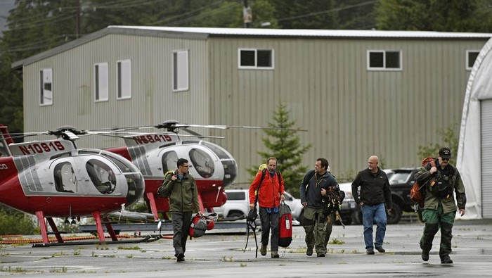 Ketchikan Volunteer Rescue Squad personnel land and disembark from a Hughes 369D helicopter on Thursday, Aug. 5, 2021, at Temsco Helicopters Inc in Ketchikan, Alaska. The KVRS, U.S. Coast Guard, Alaska State Troopers and U.S. Forest Service responded to a radio beacon alert from a downed Southeast Aviation de Havilland Beaver float plane that was carrying five passengers from the Holland America Line cruise ship Nieuw Amsterdam, according to Coast Guard, Holland America and KVRS information. The sightseeing plane crashed Thursday in southeast Alaska, killing all six people on board, the U.S. Coast Guard said. (Dustin Safranek/Ketchikan Daily News via AP)