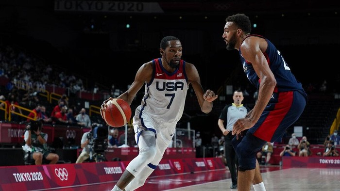 United States Kevin Durant (7) drives around Frances Rudy Gobert (27) during mens basketball gold medal game at the 2020 Summer Olympics, Saturday, Aug. 7, 2021, in Saitama, Japan. (AP Photo/Charlie Neibergall)