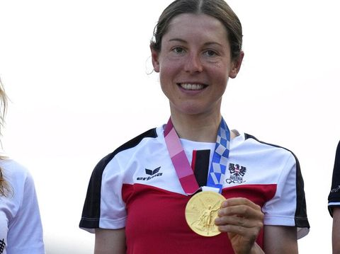 Anna Kiesenhofer of Austria holds her gold medal during a medal ceremony for the women's cycling road race at the 2020 Summer Olympics, Sunday, July 25, 2021, in Oyama, Japan. (AP Photo/Christophe Ena)