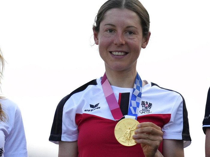 Anna Kiesenhofer of Austria holds her gold medal during a medal ceremony for the womens cycling road race at the 2020 Summer Olympics, Sunday, July 25, 2021, in Oyama, Japan. (AP Photo/Christophe Ena)