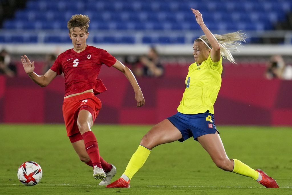Canada's Quinn, left, and Sweden's Hanna Glas battle for the ball in the women's soccer match for the gold medal at the 2020 Summer Olympics, Friday, Aug. 6, 2021, in Yokohama, Japan. (AP Photo/Fernando Vergara)