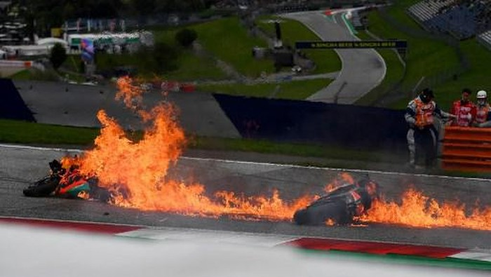 Motorbikes are on fire following a crash involving Aprilia Italian rider Lorenzo Savadori and KTM Spanish rider Dani Pedrosa after the start of the Styrian Motorcycle Grand Prix at the Red Bull Ring race track in Spielberg, Austria on August 8, 2021. (Photo by JOE KLAMAR / AFP)