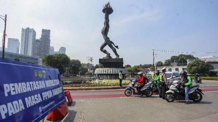 Petugas kepolisian memeriksa kendaraan di tempat penyekatan  Pemberlakuan Pembatasan Kegiatan Masyarakat (PPKM) Darurat di kawasan JalanJenderal Sudirman, Jakarta, Sabtu (17/7/2021). Menurut  Menko PMK Muhadjir Effendy Pemberlakuan Pembatasan Kegiatan Masyarakat (PPKM) Darurat akan diperpanjang hingga akhir Juli.   ANTARA FOTO/ Reno Esnir/nz