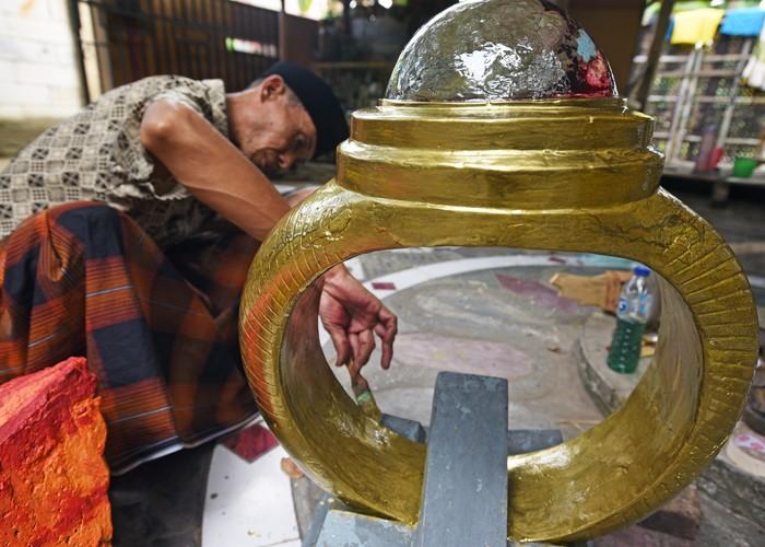 Perajin mengecat replika cincin kalimaya ukuran raksasa yang terbuat dari barang bekas di Kampung Sukawana, Serang, Banten, Senin (9/8/2021). Perajin yang juga berprofesi sebagai pengepul barang bekas memanfaatkan sebagian limbah logam dan plastik yang terkumpul untuk membuat sejumlah kreasi. ANTARA FOTO/Asep Fathulrahman/hp.
