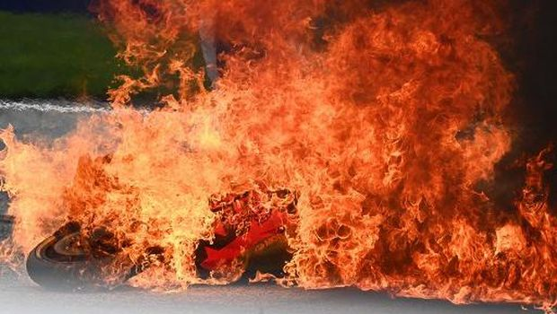 A motorbike is seen on fire following a crash involving Aprilia Italian rider Lorenzo Savadori and KTM Spanish rider Dani Pedrosa after the start of the Styrian Motorcycle Grand Prix at the Red Bull Ring race track in Spielberg, Austria on August 8, 2021. (Photo by Joe Klamar / AFP)