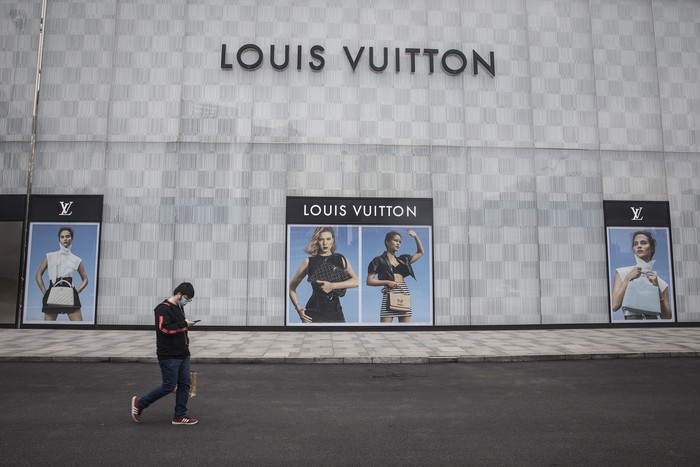WUHAN, CHINA - MARCH 30: (CHINA OUT) A man wearing a face mask passes a Louis Vuitton store outside Wuhan international plaza on March 30, 2020 in Hubei Province, China. Wuhan, the central Chinese city where the coronavirus (COVID-19) first emerged last year, will lift the lockdown on April 8, local media reported. (Photo by Getty Images)