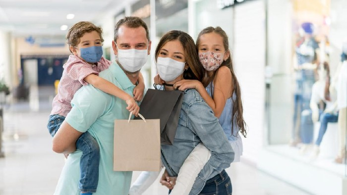 Portrait of a happy Latin American family shopping at the mall wearing facemasks during the COVID-19 pandemic – reopening of businesses concepts