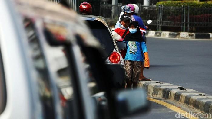 Dua anak menawarkan jasa membersihkan kaca mobil di perempatan lampu merah di Kota Bekasi. Di masa pertumbuhan, mereka terpaksa bekerja karena suatu keadaan.
