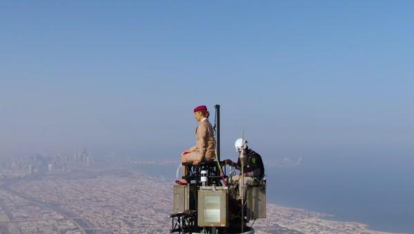 Aksinya berdiri di gedung tertinggi dunia itu dibantu oleh kalangan profesional.