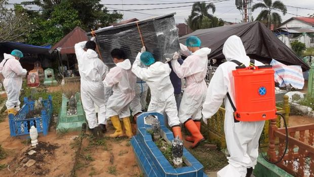 Tim KBR Brimob Polda Kalimantan Selatan membantu memakamkan jenazah pasien COVID-19. (ANTARA/Firman)