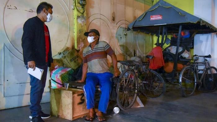 Relawan dari Gerakan Gotong Royong Nasional Pengendalian COVID-19 bersama relawan Gerakan Perjuangan Pemulung Indonesia (GaPPI) melakukan pendataan terhadap tunawisma di kawasan Jalan Nimbung, Medan Petisah, Kota Medan, Sumatera Utara, Selasa (10/8/2021) malam. Pendataan tersebut bertujuan untuk membantu masyarakat rentan, tuna wisma, gelandangan, pengemis dan anak jalanan yang tidak memiliki Nomor Induk Kependudukan (NIK) agar mendapatkan vaksin COVID-19 dalam rangka membantu Pemerintah mempercepat proses vaksinasi. ANTARA FOTO/Fransisco Carolio/Lmo/wsj.
