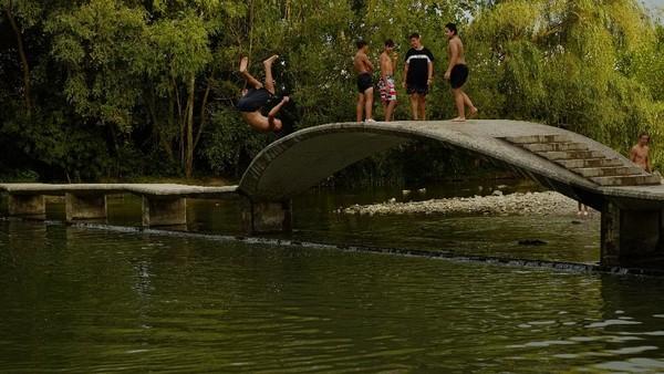 Sebagian warga memilih melompat dari jembatan dan bermain di sungai. AP Photo/Alvaro Barrientos