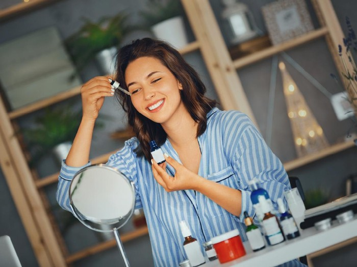 Young woman applying serum on her face while looking at mirror..