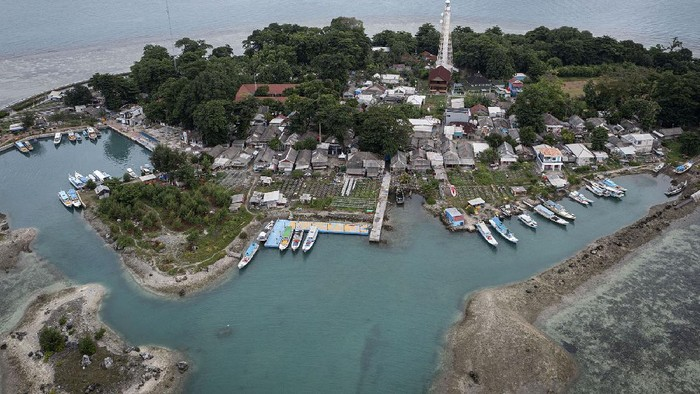 Seorang mantan nelayan Haji Hendrik (40) yang kini menjadi petugas Dinas Lingkungan Hidup DKI Jakarta menjaring sampah yang terdampar di pesisir Pulau Sabira. Hendrik bersama tujuh temannya direkrut menjadi petugas pembersih sampah pantai sejak 2020.